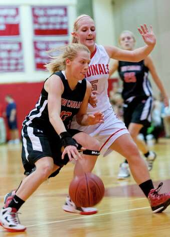 New Canaan high school's Elizabeth Miller tries to drive past Greenwich high school's Rebecca DeCarlo in a girls basketball game played at Greenwich high school, Greenwich, CT on Wednesday December 5th, 2012. Photo: Mark Conrad / Stamford Advocate Freelance