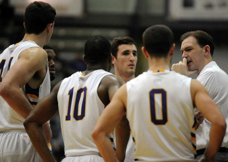 UAlbany's head coach Will Brown, right, talks with his team during their game against St. Francis in