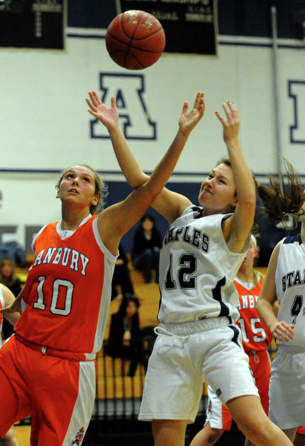 Danbury's #10 Fallon Bottone, left, and Staples #12 Kellie Green reach for a rebound, during girls basketball action in Westport, Conn. on Wednesday December 5, 2012. Photo: Christian Abraham / Connecticut Post