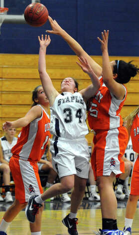 Staples' #34 Erica Stein gets blocked by Danbury's #25 Kayla Handberry as she attempts a basket, during girls basketball action in Westport, Conn. on Wednesday December 5, 2012. Photo: Christian Abraham / Connecticut Post