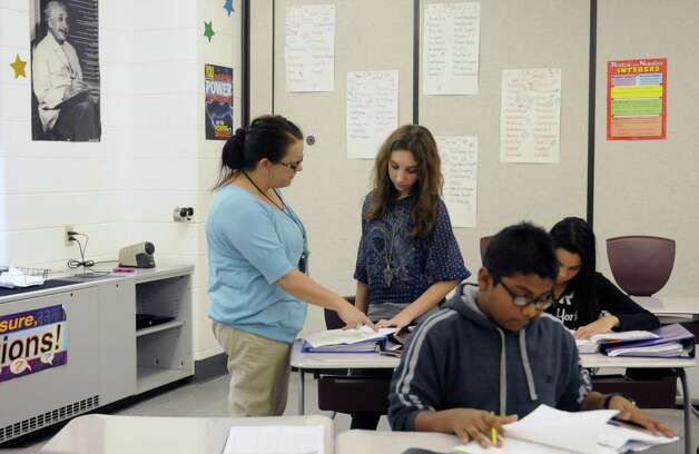 Math teacher Kerry Degnan, center/left, helps Bianca DelGiacco during a 7th grade after school math homework help class at Watervliet Junior Senior High School in Watervliet, NY Tuesday Dec. 4, 2012. (Michael P. Farrell/Times Union) Photo: Michael P. Farrell