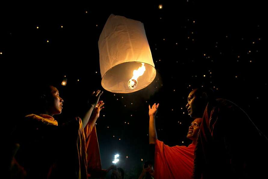 Thai monks light a lantern and release it to the night sky during celebrations to pay respect to Tha