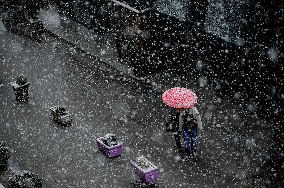 A couple walk under an umbrella during a heavy snowfall in Pristina on December 5, 2012. Photo: Armend Nimani, AFP/Getty Images