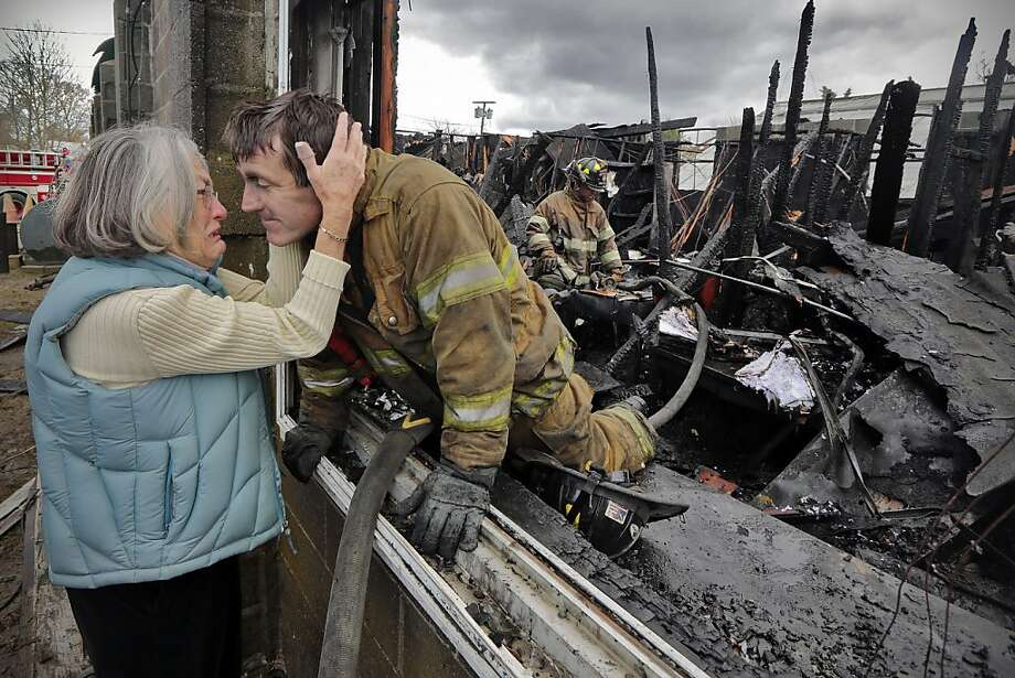 Ruth Nicolaci, left, hugs her son and firefighter Lt. G. Bourne Knowles Wednesday, Dec. 5, 2012, for the first time since learning that the landscaping business that she started with Mr. Knowles' father had been destroyed by fire in Fairhaven, Mass.  Lt. Knowles, a volunteer firefighter, was among those who fought the four-alarm fire at the landscaping business that was started by his parents. Photo: Peter Pereira, Associated Press