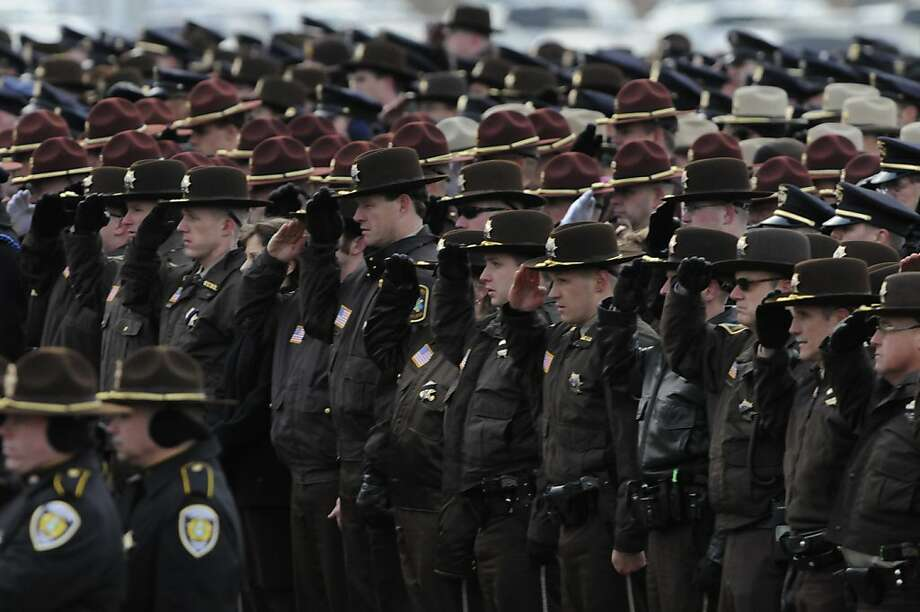 Hundreds of police officers and other aw enforcement officers saluted at burial service for Cold Spring Police Officer Tom Decker at St. Nicholas Catholic Cemetery Wednesday, Dec. 5, 2012 in St. Nicholas, Minn. Decker was shot and killed while on duty last week outside a Cold Spring, Minn., bar in what officials called an ambush. Photo: Jim Mone, Associated Press