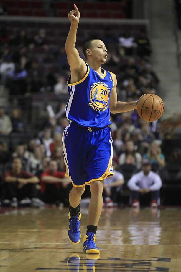 Golden State Warriors guard Stephen Curry (30) signals as he dribbles during the first quarter of an NBA basketball game against the Detroit Pistons at the Palace of Auburn Hills, Mich., Wednesday, Dec. 5, 2012. (AP Photo/Carlos Osorio) Photo: Carlos Osorio, Associated Press