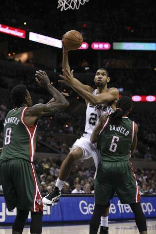 San Antonio Spurs' Tim Duncan drives through Milwaukee Bucks' Larry Sanders, left, and Marquis Daniels during the first half at the AT&T Center, Wednesday, Nov. 5, 2012. (Jerry Lara / San Antonio Express-News)