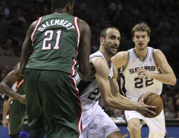 San Antonio Spurs' Manu Ginobili drives around Milwaukee Bucks' Samuel Dalembert during the first half at the AT&T Center, Wednesday, Nov. 5, 2012. In back is Tiago Splitter. (Jerry Lara / San Antonio Express-News)