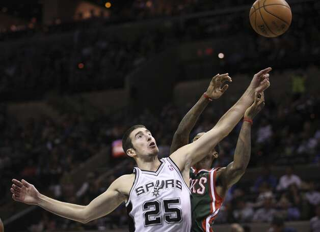 San Antonio Spurs' Nando De Colo reaches for a pass under pressure from Milwaukee Bucks' Brandon Jennings during the second half at the AT&T Center, Wednesday, Nov. 5, 2012. The Spurs won 110-99. (Jerry Lara / San Antonio Express-News)