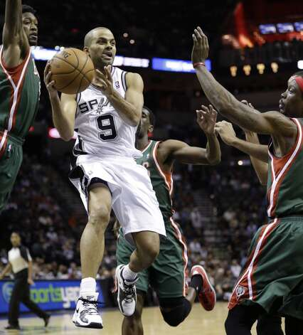San Antonio Spurs' Tony Parker (9), of France, drives between Milwaukee Bucks' Larry Sanders,left, and Marquis Daniels, right, during the first quarter of an NBA basketball game on Wednesday, Dec. 5, 2012, in San Antonio. San Antonio won 110-99. (Eric Gay / Associated Press)