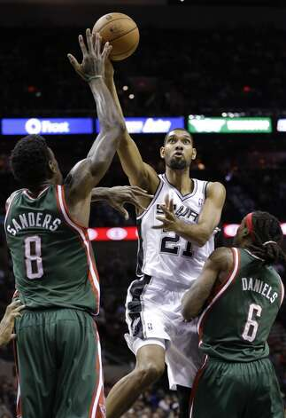San Antonio Spurs' Tim Duncan (21) drives between Milwaukee Bucks' Larry Sanders (8) and Marquis Daniels (6) during the first quarter of an NBA basketball game on Wednesday, Dec. 5, 2012, in San Antonio. San Antonio won 110-99. (Eric Gay / Associated Press)
