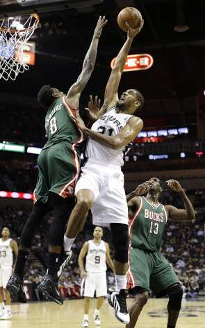 San Antonio Spurs' Tim Duncan, center, shoots over Milwaukee Bucks' Larry Sanders (8) as Ekpe Udoh (13) looks on during the first quarter of an NBA basketball game on Wednesday, Dec. 5, 2012, in San Antonio. San Antonio won 110-99. (Eric Gay / Associated Press)