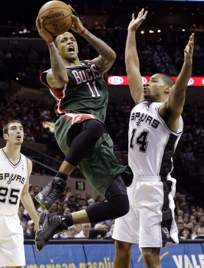 Milwaukee Bucks' Monta Ellis (11) drives past San Antonio Spurs defenders Gary Neal (14) and Nando De Colo (25) during the third quarter of an NBA basketball game on Wednesday, Dec. 5, 2012, in San Antonio. San Antonio won 110-99.  (Eric Gay / Associated Press)