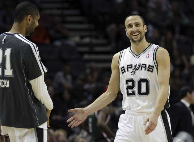 San Antonio Spurs' Tim Duncan, left, celebrates with teammate Manu Ginobili (20), of during the fourth quarter of an NBA basketball game against the Milwaukee Bucks, Wednesday, Dec. 5, 2012, in San Antonio. San Antonio won 110-99.  (Eric Gay / Associated Press)