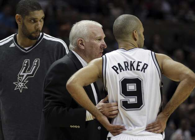 San Antonio Spurs head coach Gregg Popovich, center, talks with Tony Parker (9) and Tim Duncan, left, during the fourth quarter of an NBA basketball game against the Milwaukee Bucks, Wednesday, Dec. 5, 2012, in San Antonio. San Antonio won 110-99.  (Eric Gay / Associated Press)