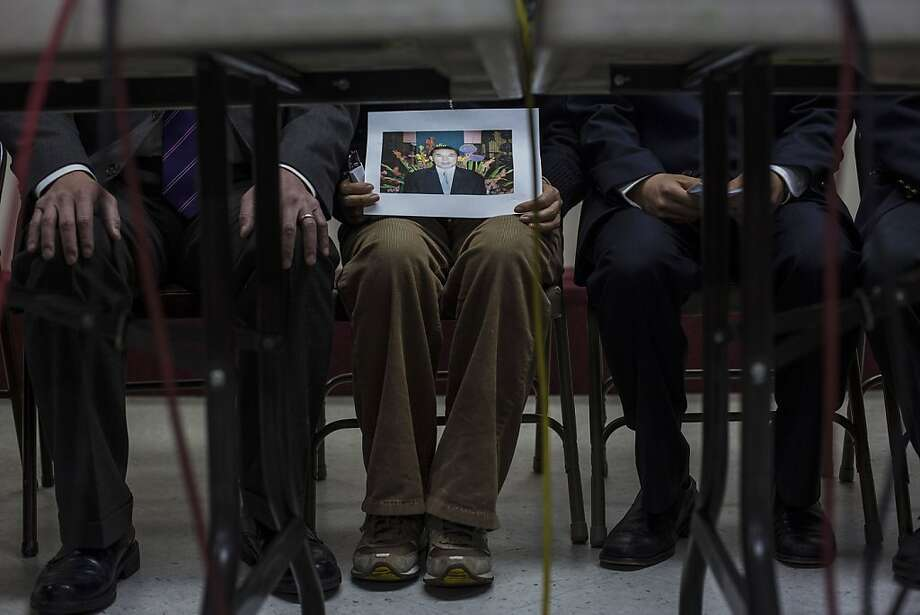 At a news conference at her church, Serim Han (center) holds a photo of her husband, Ki-Suck Han, who was pushed in front of a subway train on Monday. Photo: Uli Seit, New York Times