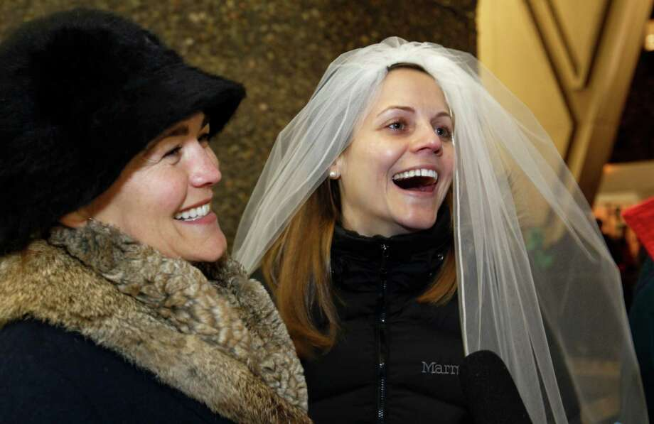 Amy Andrews, right, smiles as she wears a veil while standing in line with her partner Jeri Andrews. Photo: AP