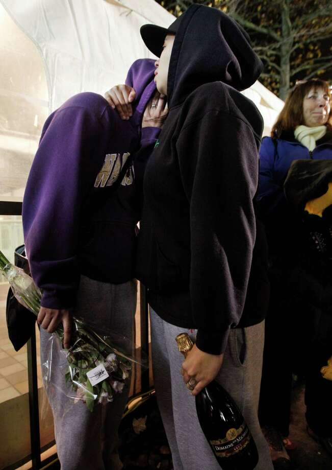 Amanda Dollente, left, and her partner Kelly Middleton, both of Auburn, Wash., wait with flowers and champagne as first in line. Photo: AP