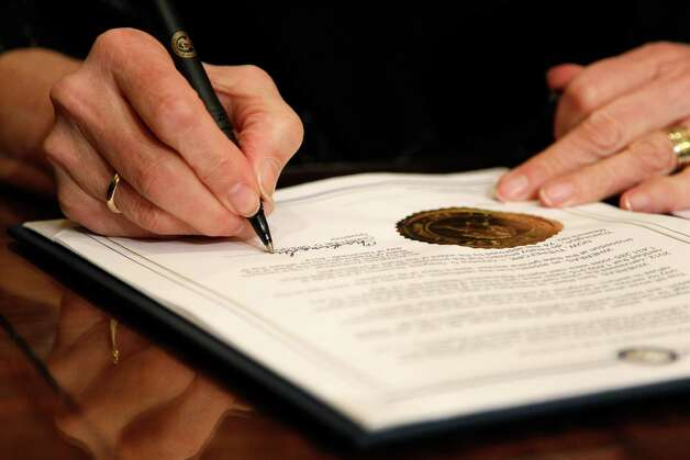 Gov. Chris Gregoire signs Referendum 74, a citizen-passed measure that legalizes same-sex marriage in the state, Wednesday, Dec. 5, 2012, in Olympia, Wash. Gregoire and Reed both signed the document at the ceremony, which allows gay couples to marry beginning Dec. 9. Photo: AP
