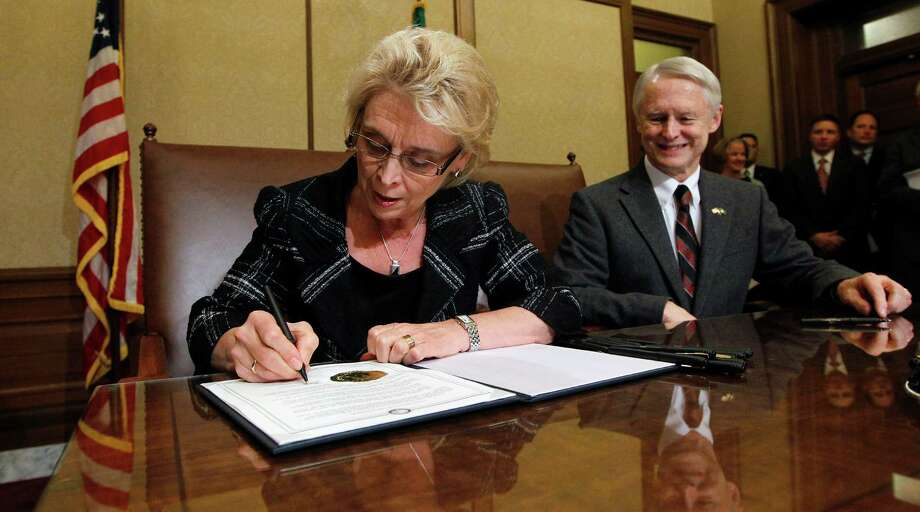As Secretary of State Sam Reed, right, looks on, Gov. Chris Gregoire signs Referendum 74, a citizen-passed measure that legalizes same-sex marriage in the state, Wednesday, Dec. 5, 2012, in Olympia, Wash. Gregoire and Reed both signed the document at the ceremony, which allows gay couples to marry beginning Dec. 9. Photo: AP