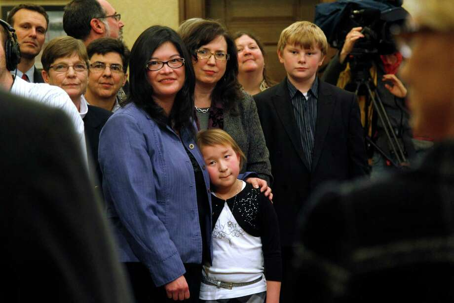 Heather Kawamoto, center left, and her partner Kay Lancaster stand with their daughter, Kayleigh Kawamoto, 9, during a signing ceremony for Referendum 74,  a citizen-passed measure that legalizes same-sex marriage, Wednesday, Dec. 5, 2012, in Olympia, Wash. Gay couples can marry beginning Dec. 9. Kawamoto and Lancaster are planning to wed that day. Photo: AP