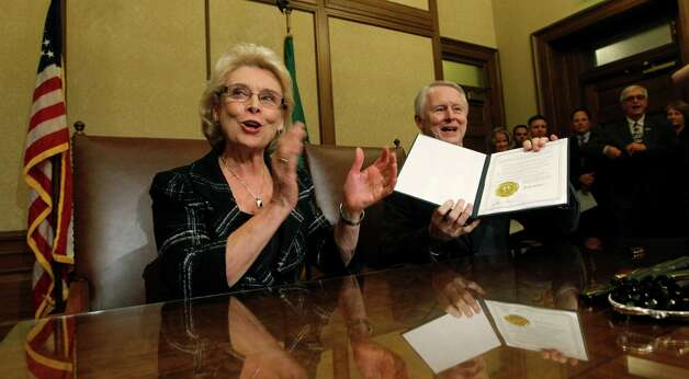Gov. Chris Gregoire, left, applauds as Secretary of State Sam Reed holds up the signed certification of Referendum 74,  a citizen-passed measure that legalizes same-sex marriage in the state, Wednesday, Dec. 5, 2012, in Olympia, Wash. Gregoire and Reed both signed the document at the signing ceremony, which allows gay couples to marry beginning Dec. 9. Photo: AP