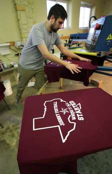 Scott Klingle of San Saba Cap in Kerrville, Tx, smooths out a t-shirt on a machine printing t-shirt for Wing King Restaurant, to be used in promotions Saturday night during a Heisman Trophy Awards watching party. Hometown football hero Johnny Manziel, who attended Tivy High School, is a candidate for the Heisman Trophy. Wednesday, Dec. 5, 2012. Photo: Bob Owen, San Antonio Express-News / © 2012 San Antonio Express-News