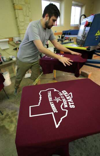Scott Klingle of San Saba Cap in Kerrville, Tx, smooths out a t-shirt on a machine printing t-shi