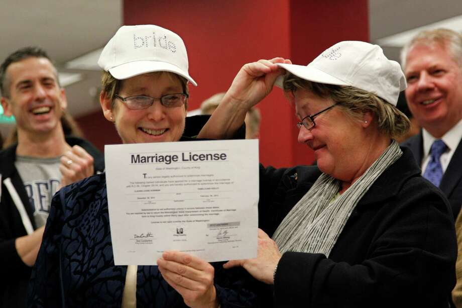 "Claudia Gorbman, left, and partner Pam Keeley wear caps both reading ""bride"" as they display their newly-issued marriage license. Photo: AP"