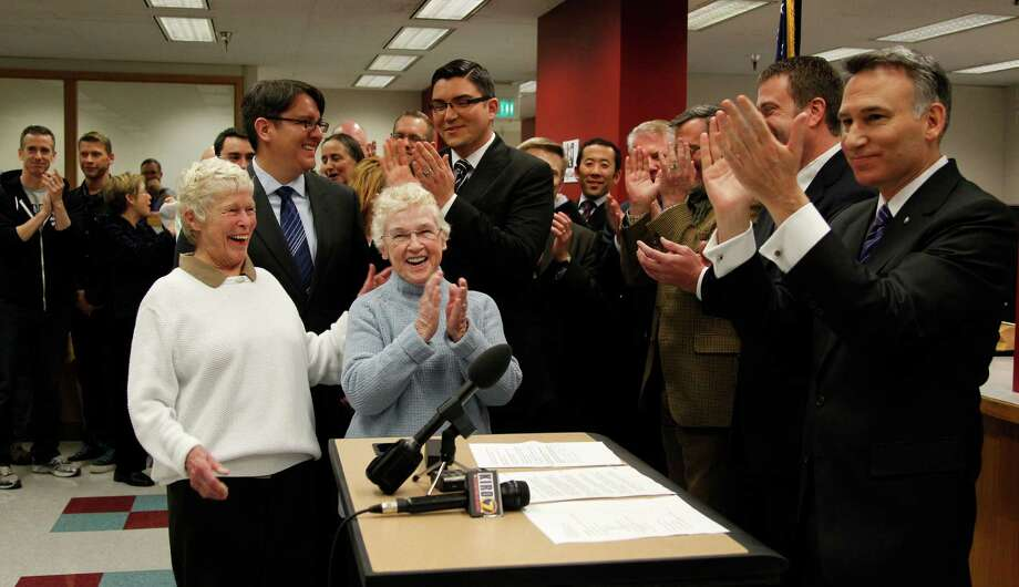 King County Executive Dow Constantine, right , leads a cheer as the clock strikes midnight and he can begin to issue marriage licenses to same-sex couples lined-up. Photo: AP