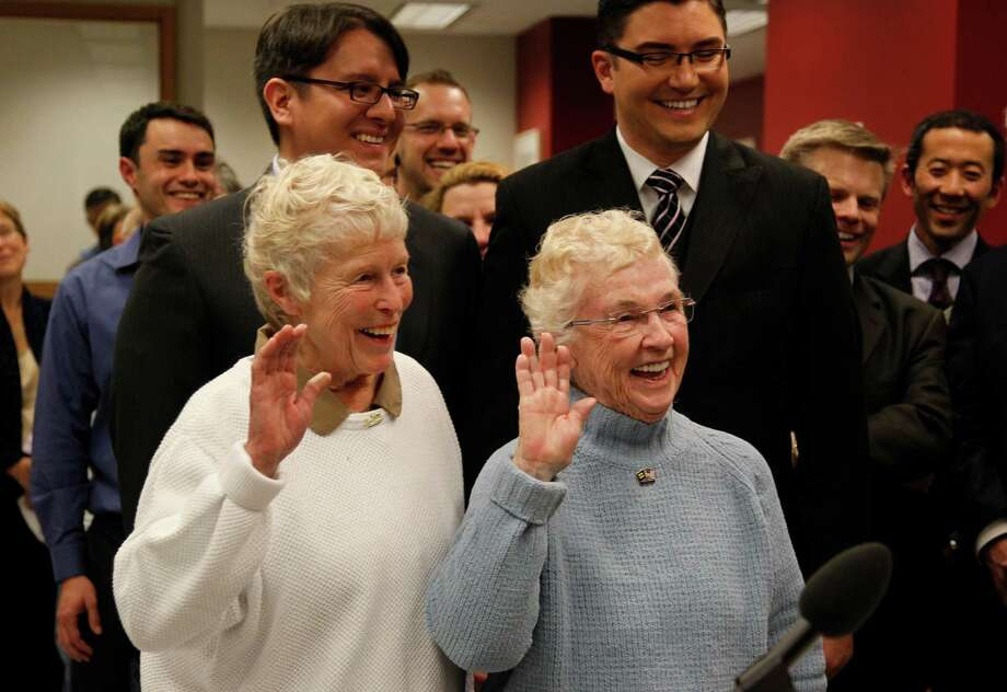 Jane Abbott Lighty, left, and her partner Pete-e Petersen raise their right hands as they take an oath while receiving the first marriage license for a same-sex couple in King County. Photo: AP