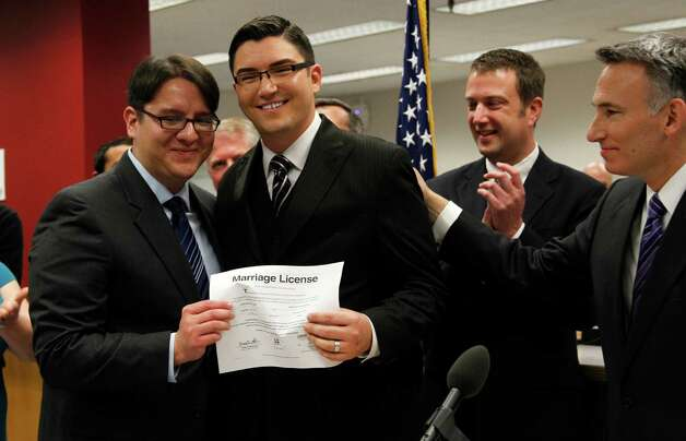 Brendon K. Taga, left, and partner Jesse Page display their marriage license issued by King County Executive Dow Constantine. Photo: AP