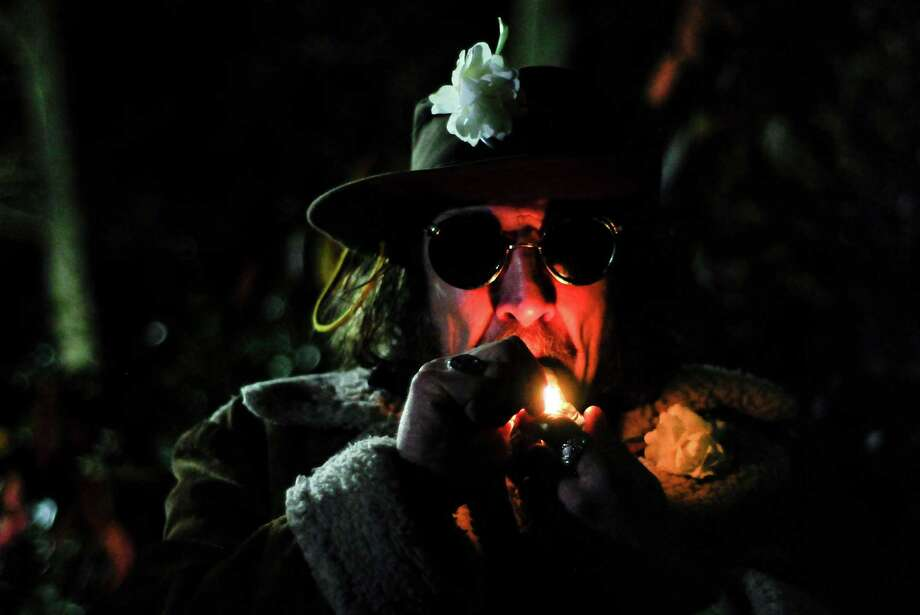 Professor Gizmo, 50, lights up as he waits for I-502 to take effect at the Space Needle on Wednesday, December 5, 2012. Washington State voters approved I-502 on November 6, but the law did not go into effect until today. An ounce of marijuana is now legal for adults over 21 in Washington. Photo: LINDSEY WASSON / SEATTLEPI.COM