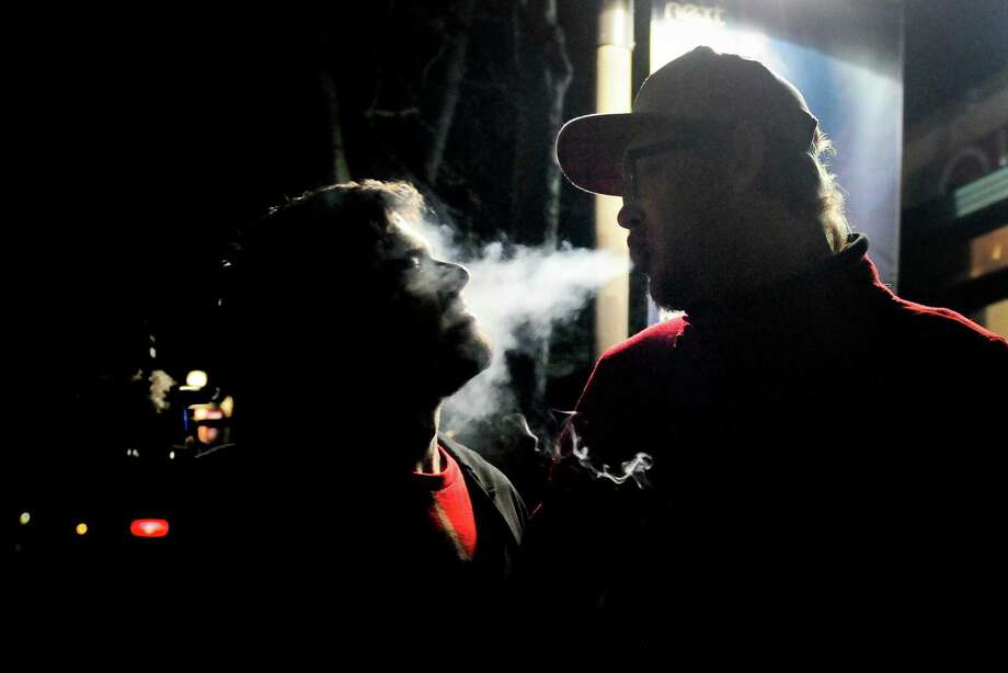Joe Riley, left, smiles as his boyfriend T.J. Underwood, right, blows marijuana smoke into his face at the Space Needle on Thursday, December 6, 2012. Washington State voters approved I-502 on November 6, but the law did not go into effect until today. An ounce of marijuana is now legal for adults over 21 in Washington. Photo: LINDSEY WASSON / SEATTLEPI.COM