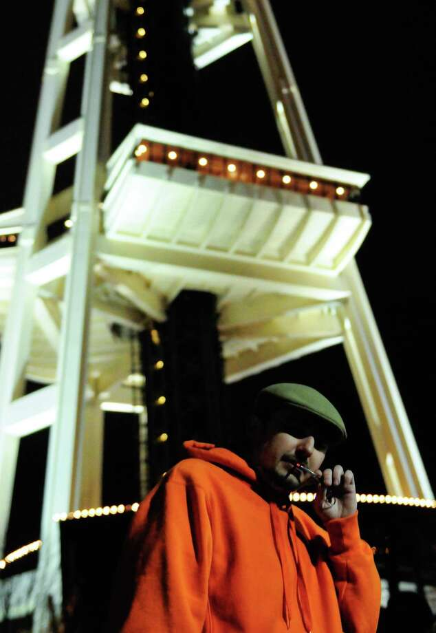 Spencer W. takes a drag at the Space Needle on Thursday, December 6, 2012. Washington State voters approved I-502 on November 6, but the law did not go into effect until today. An ounce of marijuana is now legal for adults over 21 in Washington. Photo: LINDSEY WASSON / SEATTLEPI.COM
