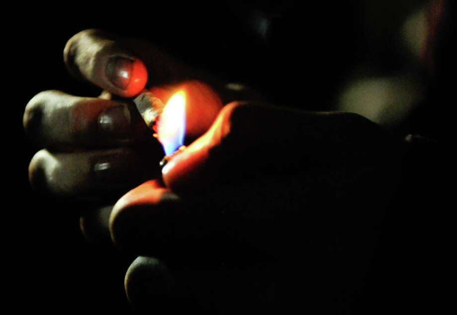 A man lights a joint a few minutes after the official legalization of marijuana in Washington at the Space Needle on Thursday, December 6, 2012. Washington State voters approved I-502 on November 6, but the law did not go into effect until today. An ounce of marijuana is now legal for adults over 21 in Washington. Photo: LINDSEY WASSON / SEATTLEPI.COM