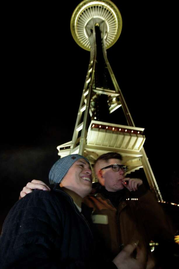 David DesRoaches, left, and Michael Hodges, right, pose for a friend's photo as they smoke marijuana, Thursday, Dec. 6, 2012, just after midnight at the Space Needle in Seattle. Possession of marijuana became legal in Washington state at midnight, and several hundred people gathered at the Space Needle to smoke and celebrate the occasion, even though the new law does prohibit public use of marijuana. Photo: AP