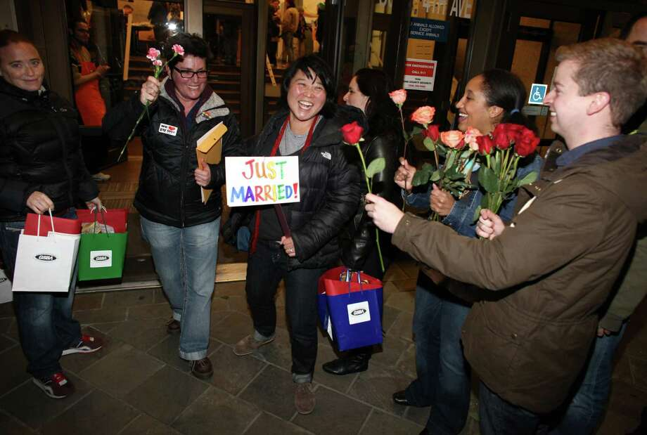 Junia Ribeiro, left, and her partner Patty Oh are greeted as the walk out of the King County Administration Building with their marriage license on Thursday, December 6, 2012. Photo: JOSHUA TRUJILLO / SEATTLEPI.COM