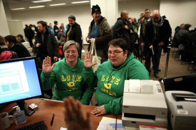 Jennifer Traband, left, and Emme Scheible give an oath that their information is accurate as same-sex couples are issued marriage licenses at the King County Administration Building shortly after midnight on Thursday, December 6, 2012. Photo: JOSHUA TRUJILLO / SEATTLEPI.COM