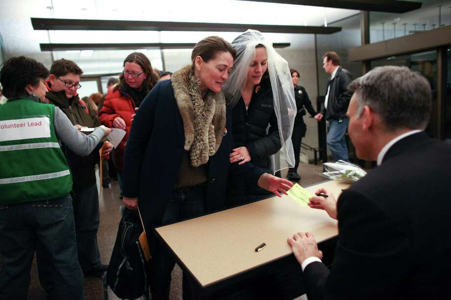 Jeri Andrews, left, and her partner of five years Amy Andrews have their marriage license signed by King County Executive Dow Constantine. Photo: JOSHUA TRUJILLO / SEATTLEPI.COM