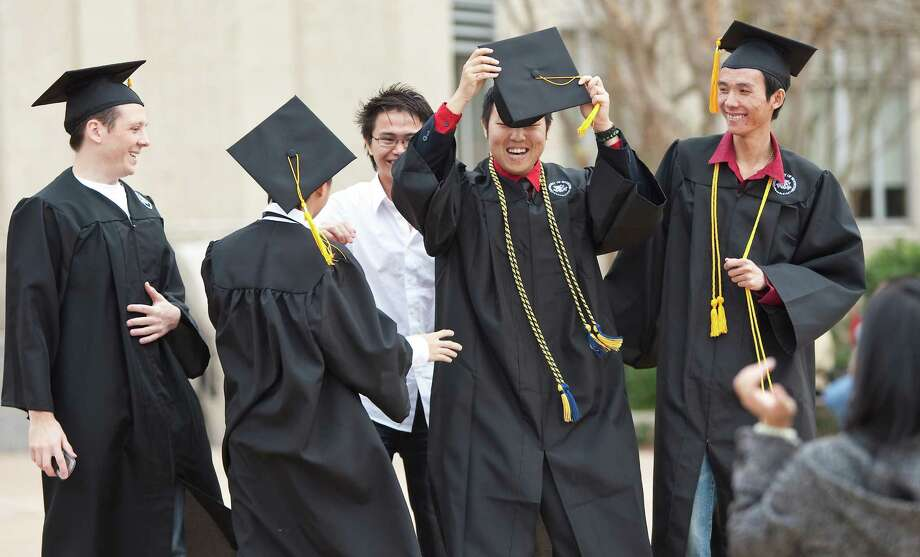 Huy N. Nguyen, center, fixes his graduation mortarboard, cap, as he and his friends pose for a graduation photo Friday, Dec. 17, 2010, by the Ezekiel W. Cullen Building on the University of Houston central campus in Houston. Steven Fippinger, left to right, Nhat Le, turned away, Nguyen, and Son Tran are getting undergraduate degrees in computer science. Photo: Nick De La Torre, Houston Chronicle / Houston Chronicle