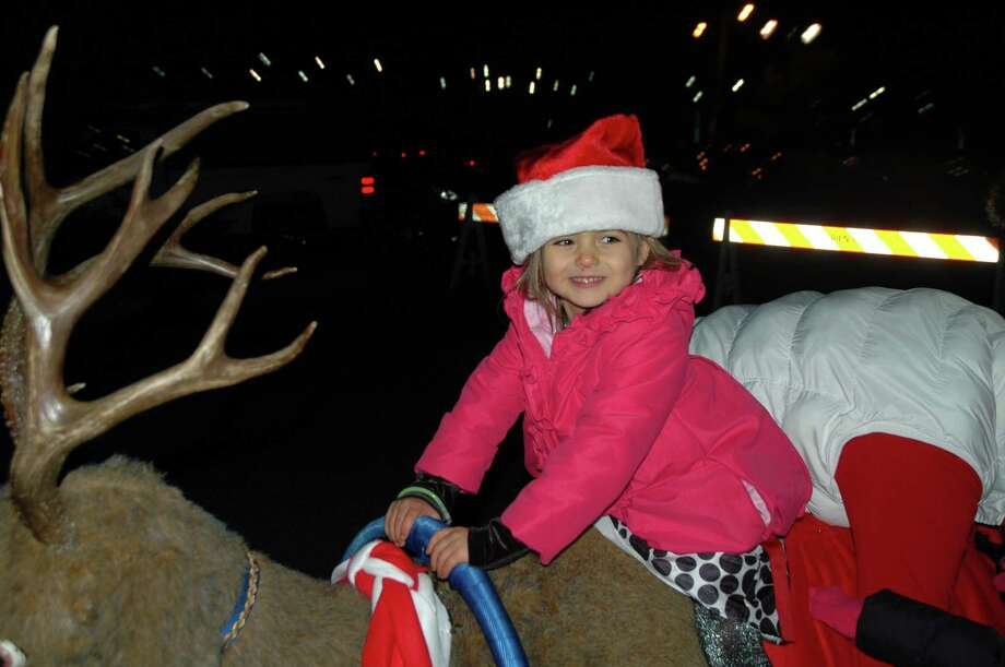 Elexa Brady takes her turn on the mechanical reindeer at Holiday Magic in Darien at Grove Street Plaza Saturday, Dec. 1, 2012. Photo by Mac McDonough Photo: Contributed Photo