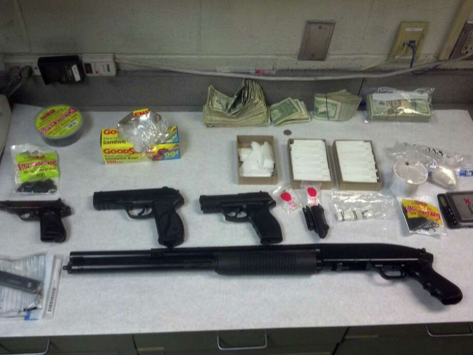 Guns, heroin and cash Troy police say were seized during a Thursday morning raid at a Ninth Street home. (Troy police photo)