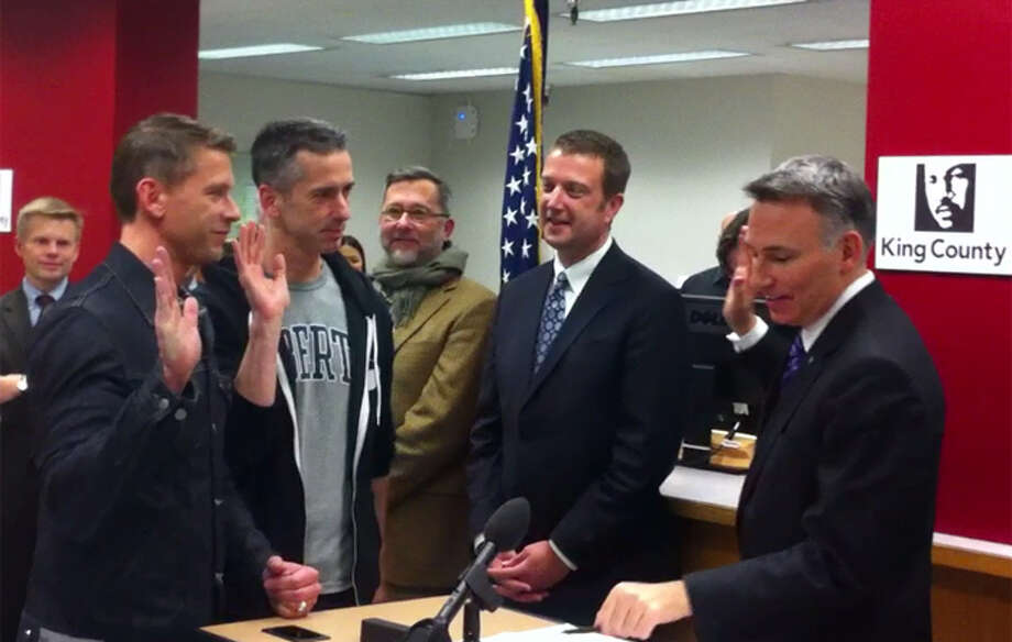 Author and columnist Dan Savage and his husband, Terry Miller, were among the first same-sex couples to receive a Washington marriage license on Thursday, Dec. 6, 2012. At right is King County Executive Dow Constantine. (Casey McNerthney/seattlepi.com)