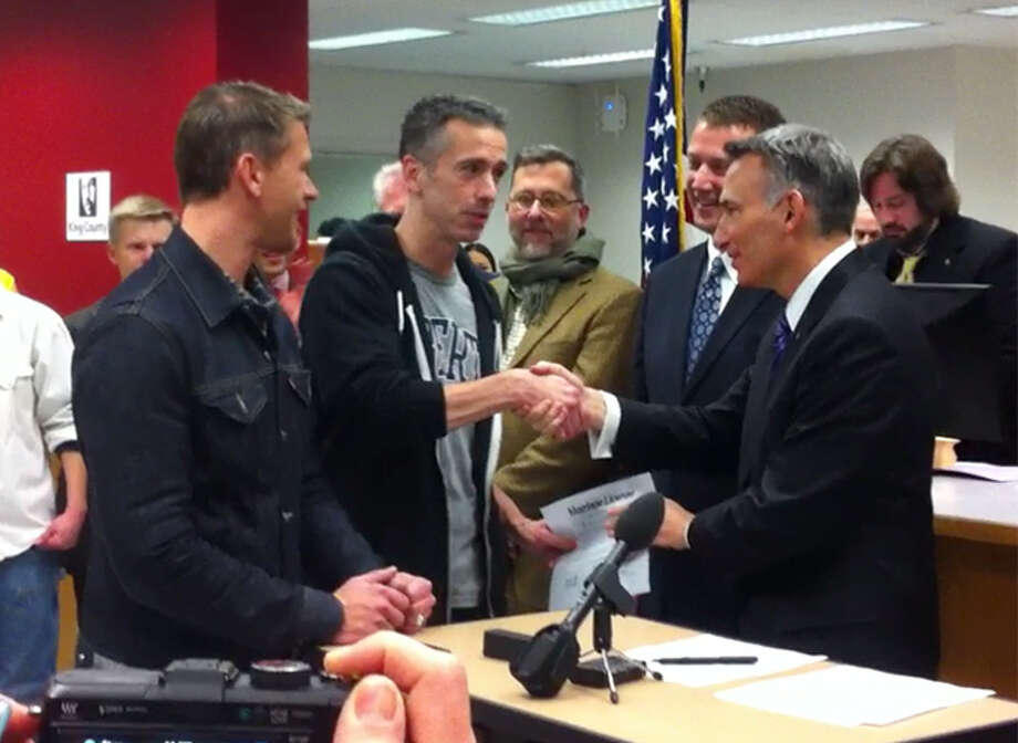 King County Executive Dow Constantine shakes hands with Dan Savage after he and his husband, Terry Miller, received their Washington marriage license. The couple previously was married in Canada in 2005. (Casey McNerthney/seattlepi.com)