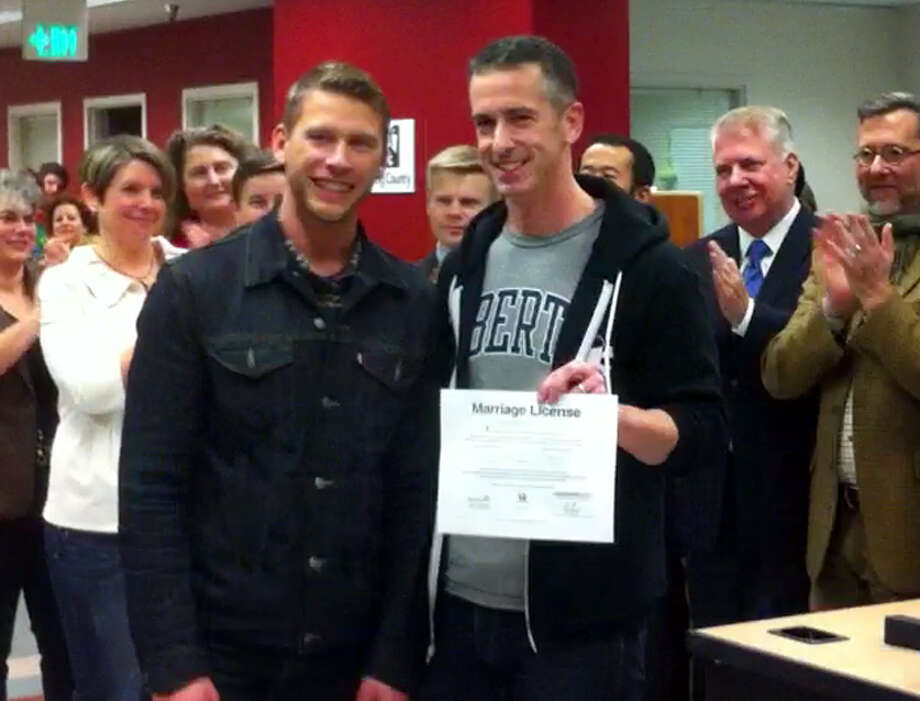 Terry Miller and Dan Savage after getting their Washington marriage license at the King County Administration Building, Dec. 6, 2012. (Casey McNerthney/seattlepi.com)