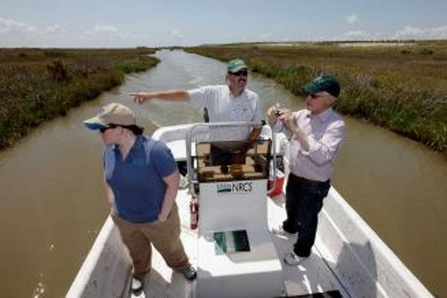 FILE - In this Tuesday, June 28, 2011 file photo, Scott Alford, center, a soil conservationist for the Natural Resources Conservation Service, points out features of a manmade marsh to Harris Sherman, right, undersecretary for natural resources and the environment at the U.S. Department of Agriculture and Julie Grogan-Brown, left, also with the USDA, near Baytown, Texas. The marsh is part of a project to restore lost wetlands and islands off the Texas coast. A report released to The Associated Press says the Natural Resources Conservation Service has already committed more than a half-billion dollars to the Gulf Coast in the past two years, nearly one-fifth of it on projects directly linked to recovery from the 2010 oil spill. Photo: David J. Phillip / AP