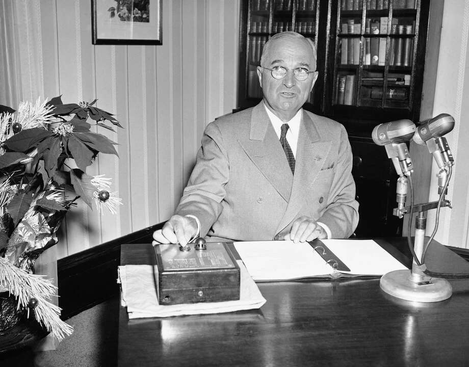 President Harry S. Truman, seated in front of bookcase at his home in Independence, Mo., pushes button which lighted the nation's Christmas tree on south lawn of White House, Washington, Dec. 24, 1949. Tree lighting came during the president's annual Christmas talk to the nation. The text of his radio talk is in the notebook in front of him. Photo: Henry Griffin, Associated Press / AP1949
