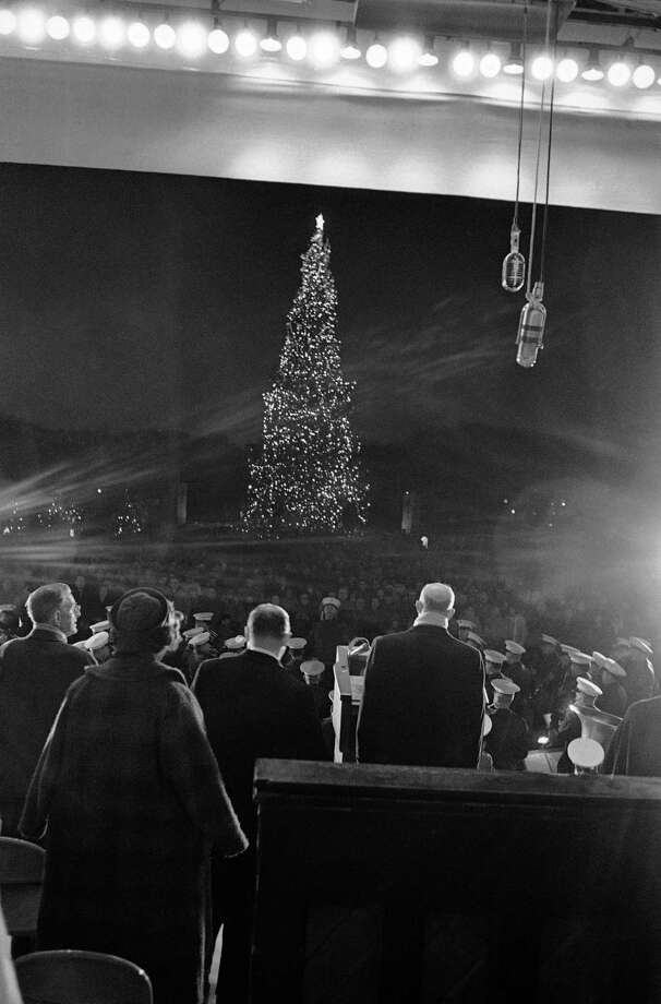 President Eisenhower, right, faces the National Christmas Tree as he lighted it in Washington formally opening the annual Christmas Pageant of Peace on Dec. 23, 1960. The tree is erected in the Ellipse, a park just south of the White House. Photo: Associated Press