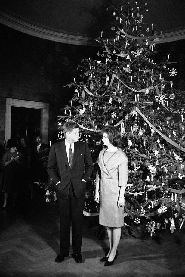 President John F. Kennedy  and Jacqueline Kennedy  pose in front of the Christmas tree in the Blue Room of the White House in Washington on Dec. 13, 1961. The occasion was a pre-Christmas party for White House staff members and their families. Photo: Associated Press
